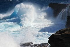 Translucent ice-blue waves crashing onto cliffs. On Hawaii, powerful trade winds sweep open ocean swells into huge black lava cliffs on Oahu's southern shoreline Royalty Free Stock Photography