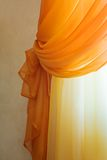 Translucent orange curtains Stock Images