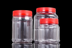 Translucent plastic PVC jar with red cover isolated in black Stock Images