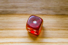 A translucent red six sided playing dice on a wooden background. A beautiful winning playing dice rolled on a side on wooden table Royalty Free Stock Photography