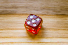 A translucent red six sided playing dice on a wooden background. A beautiful winning playing dice rolled on a side on wooden table Royalty Free Stock Photo