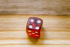 A translucent red six sided playing dice on a wooden background. A beautiful winning playing dice rolled on a side on wooden table Royalty Free Stock Image