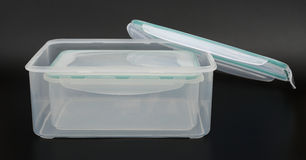 Translucent storage boxes with lip opened on black background Royalty Free Stock Photography