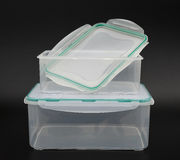 Translucent storage boxes with one opened on black background Royalty Free Stock Image