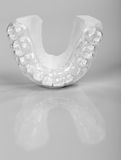 Translucent upper essix retainer on a gray background Royalty Free Stock Photo