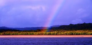 Translucent vibrant Rainbow near water. Stock Photo