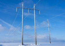Transmisión de energía eléctrica en el campo contra el cielo azul fotos de archivo libres de regalías