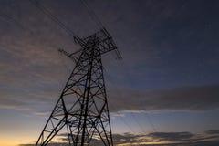 Transmissie en distributie over lange afstand van elektriciteitsconcept Hoekige mening van hoogspanningstoren met stroomlijnen st Royalty-vrije Stock Foto's