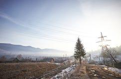 Transmission de courant électrique dans le village de mountaine pendant l'hiver Images stock