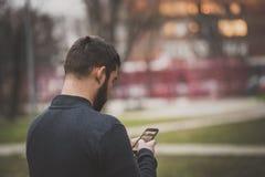 Transmission de messages belle de jeune homme un ami à son téléphone dans une zone urbaine photo libre de droits