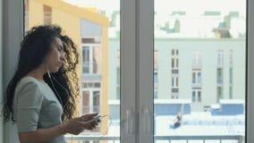 Transmission de messages bouclée de brune avec quelqu'un écoutant une musique près de la fenêtre banque de vidéos