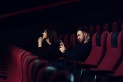 Transmission de messages d'homme avec une autre fille dans le cinéma Photos stock