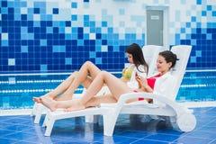Transmission de messages de jeunes amies avec l'ami sur son smartphone Station thermale de relaxation et concept social de réseau Photos libres de droits