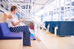 Transmission de messages femelle créative de femme d'affaires sur son smartphone tout en se reposant Photos libres de droits