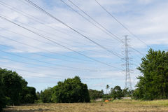 Transmission High voltage electricity pylon with blue sky backgr Stock Images