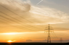 Transmission line and poles at sunset. Transmission line with sunrise and plane high in the sky Stock Images