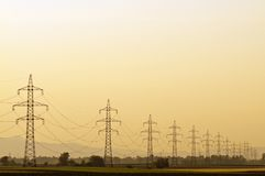 Transmission line at sunset. With clear orange sky and no end pylons stock photo