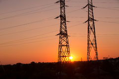 Transmission power line silhouette on sunset Stock Photos