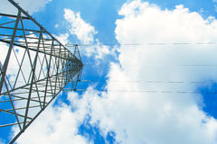 Transmission power line tower. Over blue sky with white soft clouds royalty free stock images