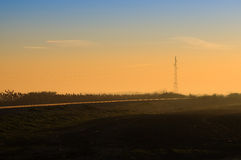 Transmission power lines tower by the railroad at sunrise Royalty Free Stock Photo