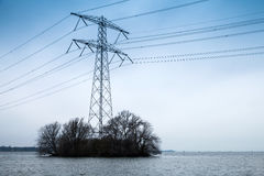 Transmission power tower, electricity pylon. Stands on small island with bare trees. Steel lattice tower, used to support an overhead power line Royalty Free Stock Images
