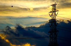 Transmission Tower. A rich sunset of golds, oranges and blues is the backdrop for this silouetted transmission tower royalty free stock image