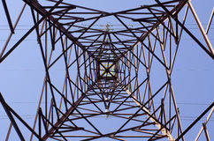 Transmission tower. As seen from below towards a blue sky royalty free stock photo
