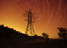 Transmission tower against star trails. Space energy: transmission tower against star trails in night sky stock photo