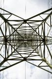 Transmission tower bottom view. Power tower on cloudy sky. Electricity pylon structure for power line. High voltage post Royalty Free Stock Photography