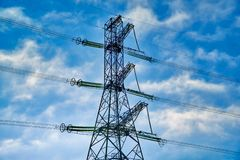 A transmission tower or electricity pylon with blue sky. It is a tall structure, usually a steel lattice tower, used to support an. Overhead power line. Moscow royalty free stock photo
