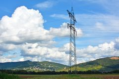 Transmission Tower in front of mountain range and blue sky with clouds royalty free stock images