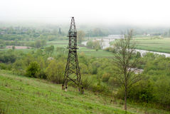 Transmission tower. Giant cloud. Bridge over river. Foggy weather. Stock Photography