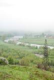 Transmission tower. Giant cloud. Bridge over river. Foggy weather. Carpathians, Ukraine. Royalty Free Stock Photo