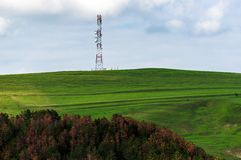 Transmission tower with green fields. And sky royalty free stock photos