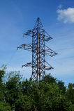 Transmission tower with green trees on background of blue sky.  stock image