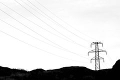 Transmission tower with high voltage wires in dark. Transmission tower with high voltage wires in a dark landscape setting stock photography