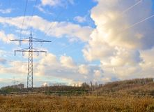 Transmission tower on a meadow. Transmission tower, or electricity pylon, in a field in front of a cloudy sky royalty free stock photo
