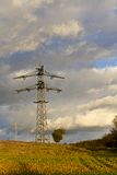 Transmission tower over a field 1. Transmission tower, or electricity pylon, in a field in front of a cloudy sky stock photos