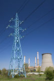 Transmission tower and power plant on a bright day Royalty Free Stock Photo