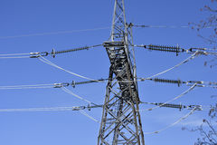 A transmission tower or power tower electricity pylon with pow. Er lines against a blue sky, showing the connection and the isolation from the steel construction royalty free stock photos