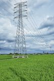Transmission tower. Pylon for overhead power lines at paddy field in Sekinchan town, west coast of Malaysia Stock Image