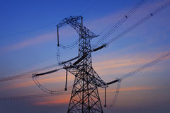 The transmission tower in the sunset. The high voltage transmission tower in the sunset stock photo