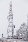 Transmission tower in winter, Telecommunications tower with cell. Ular antenna and satellite dish stock image
