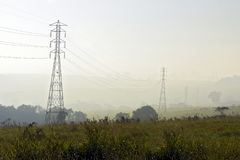 Electric power towers, under mist. Transmission towers of high-voltage electrical energetics, in the middle of the meadow with fog, in the morning light Stock Photos