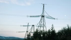 Transmission towers in mountains. Power towers against sunset sky. Electric towers in green forest at dusk.  stock video