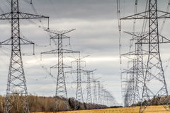 Transmission towers. A row of high voltage transmission towers in a field royalty free stock image