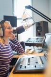 Transmissão de rádio fêmea feliz do anfitrião através do microfone Imagens de Stock