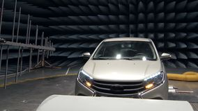 Transmitter is emitting waves on working automobile in anechoic test chamber. In car plant stock video footage