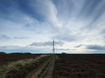 Transmitter mast on moors under brooding sky. Transmitter mast viewed from Howdale Moor under brooding sky in the North York Moors National Park, Yorkshire, UK Stock Image