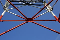 Transmitter on metal tower. Metal tower with telecommunications transmitter against blue skies Stock Image